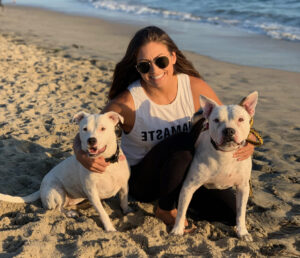 Jess at the beach posing with her dogs