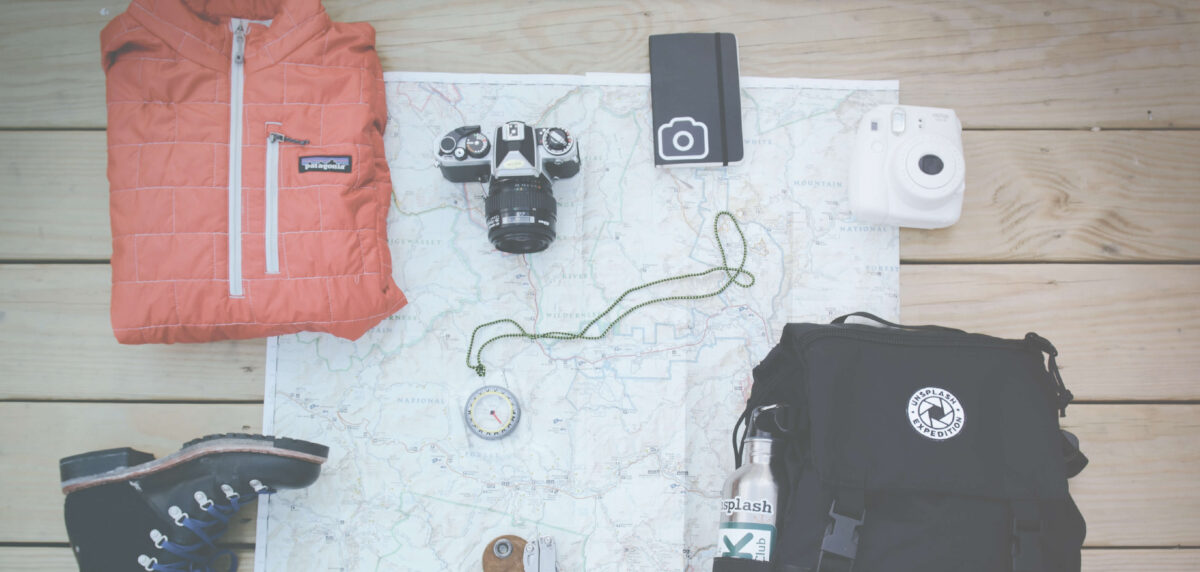flat lay with map compass camera and hiking gear